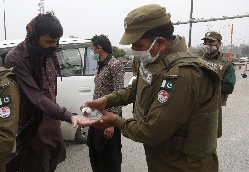 A police officers dispenses hand sanitizer in an effort to contain the coronavirus, in Lahore, Pakistan, Tuesday, March 24, 2020. Pakistani authoritie...