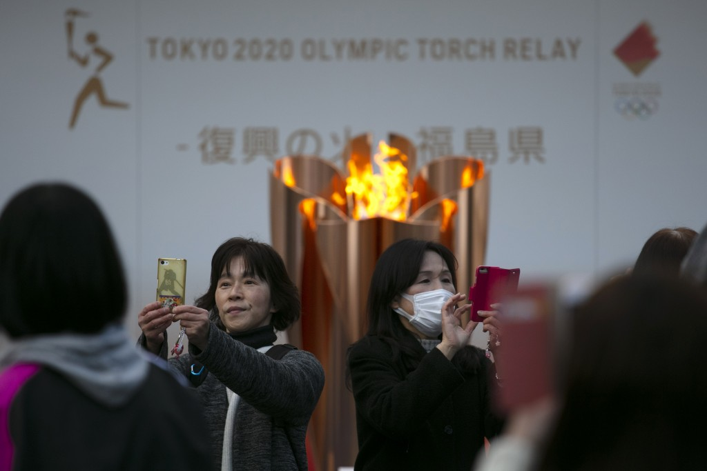 People take pictures with the Olympic Flame during a ceremony in Fukushima City, Japan, Tuesday, March 24, 2020. The Tokyo Olympic torch relay will st...