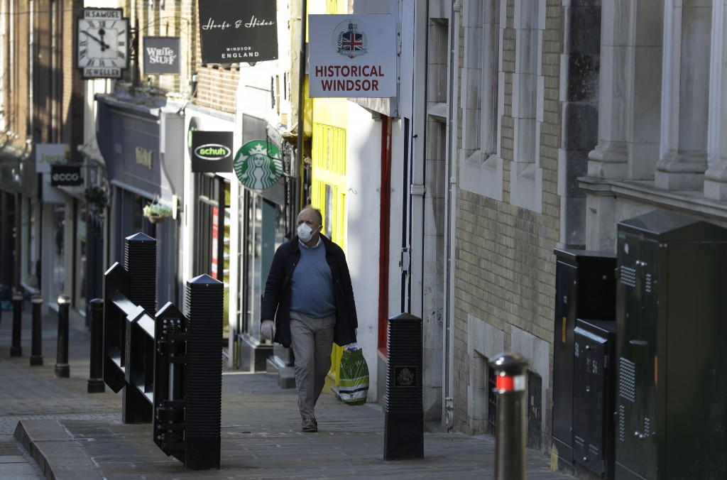 A shopper walks up an empty street near Windsor Castle in Windsor, England Tuesday, March 24, 2020. Britain's Prime Minister Boris Johnson on Monday i...