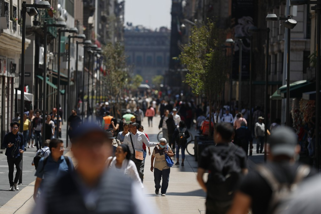 Pedestrians walk along Madero Street in Mexico City, Monday, March 23, 2020. Beginning Monday, Mexico's capital shut down museums, bars, gyms, churche...
