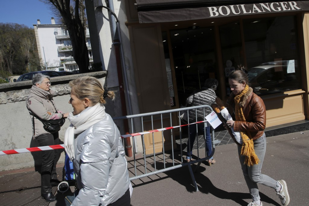 Customers queue to buy bread in a Ville d'Avray bakery, outside Paris, Tuesday, March 24, 2020. French President Emmanuel Macron urged employees to ke...