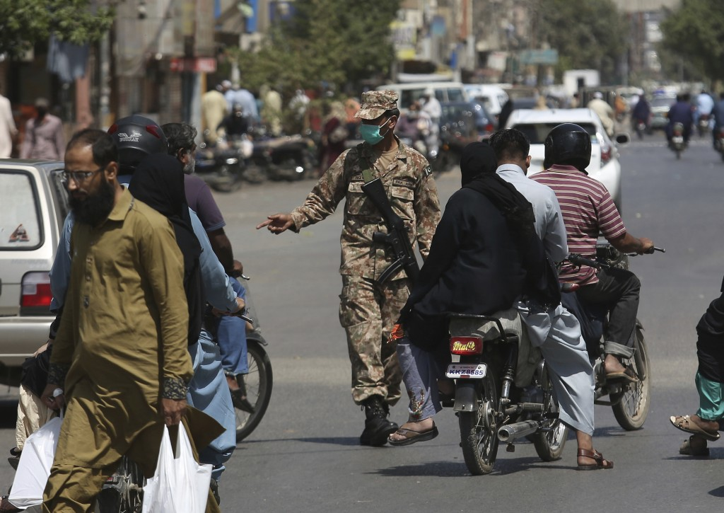 A Pakistani soldiers stops vehicles to implement a lockdown in an effort to contain the coronavirus, in Karachi, Pakistan, Tuesday, March 24, 2020. Pa...