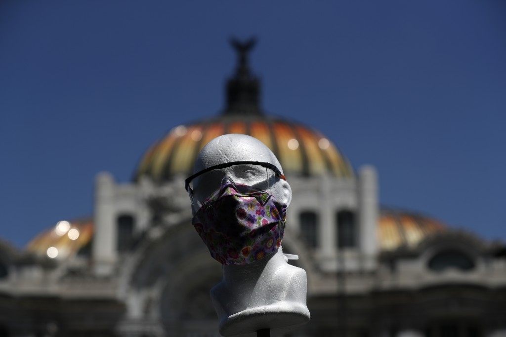 A styrofoam head models a handmade fabric face mask being sold by Jorge Rodriquez, in front of the Palace of Fine Arts in Mexico City, Monday, March 2...