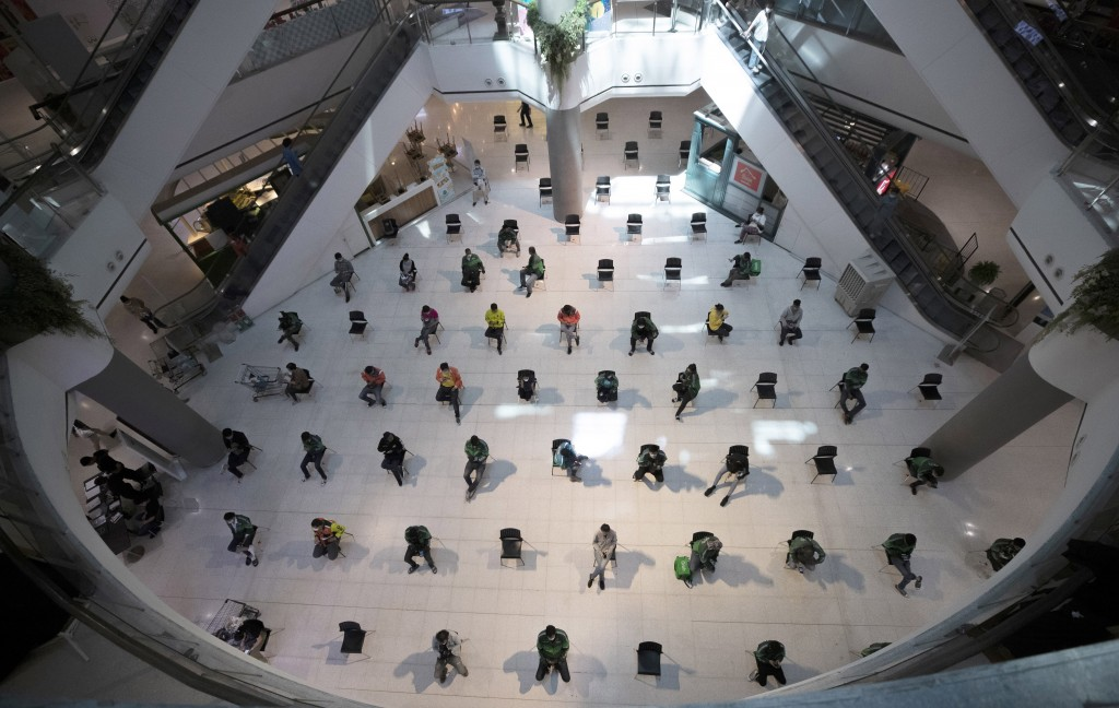 People practice social distancing as they sit on chairs spread apart in a waiting area for take-away food orders at a shopping mall in hopes of preven...