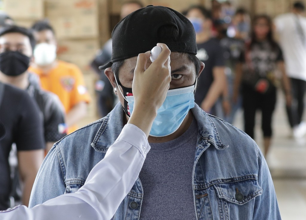 Temperatures are checked before people enter a local city hall during a community quarantine aimed to prevent the spread of the new coronavirus in Man...