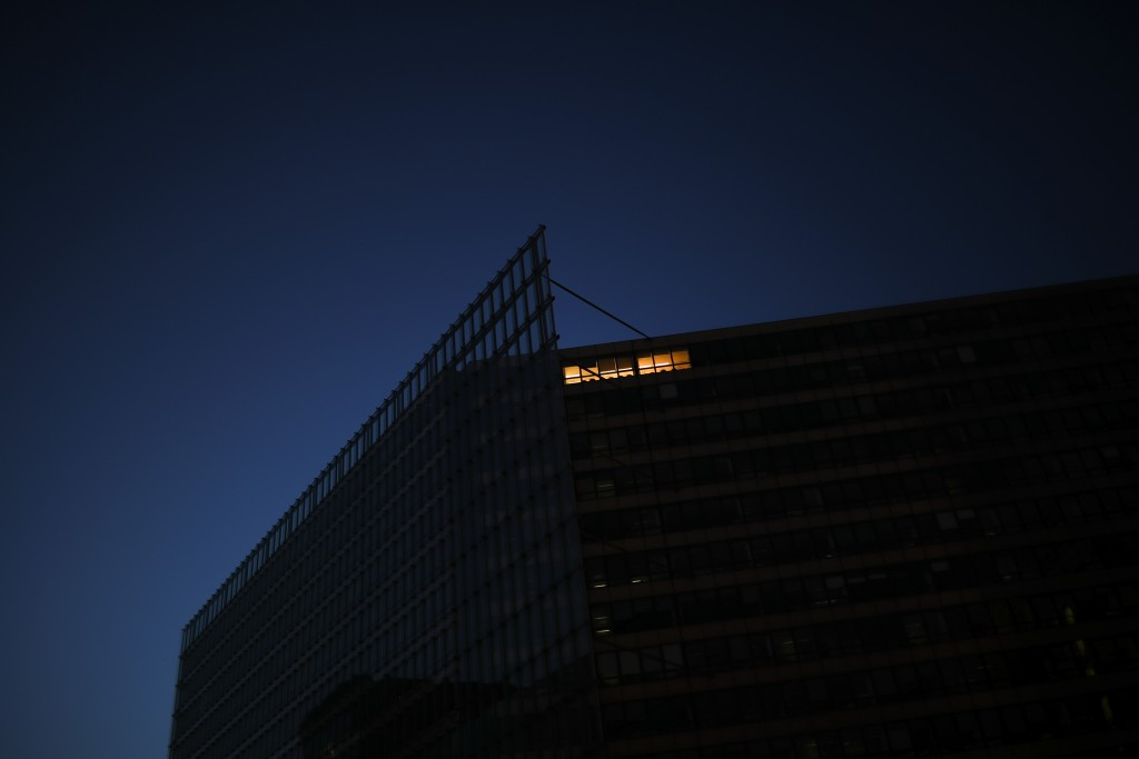 A light is on at the EU Charlemagne building during a partial lockdown ordered by Belgium government in Brussels, Monday, March 23, 2020. For some peo...