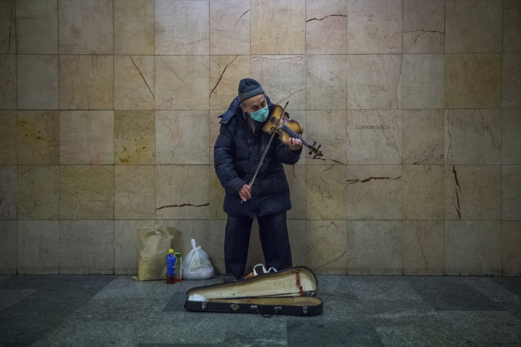 Busker wearing a protective face mask plays the violin in the subway at Nyugati Square during the coronavirus emergency in Budapest, Hungary, March 18...