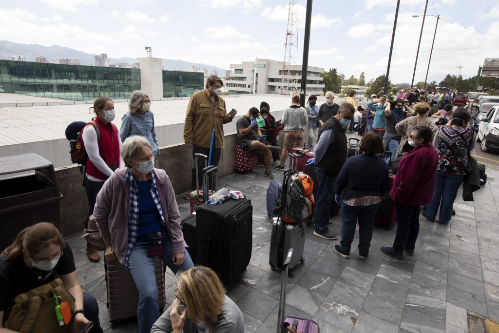 Travelers wait to take a charter flight coordinated by the U.S. embassy at La Aurora airport in Guatemala City, Monday, March 23, 2020. American citiz...