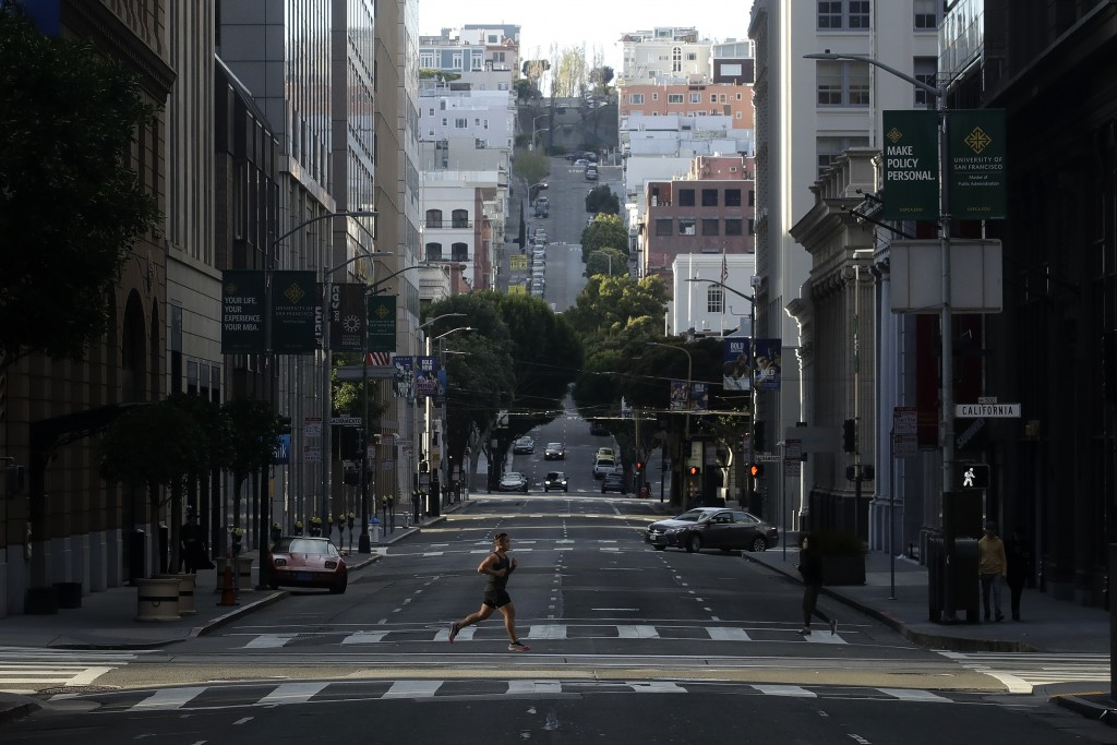 A man runs across a near empty Montgomery Street in San Francisco, March 21, 2020. (AP Photo/Jeff Chiu)