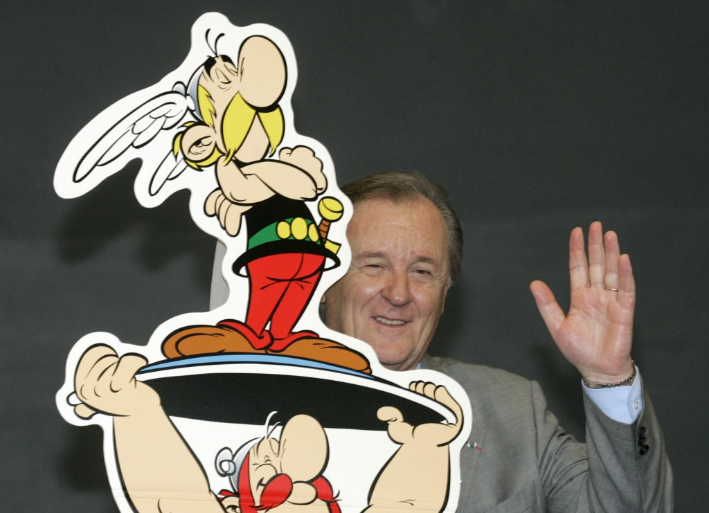 FILE - In this Oct.23, 2005 file photo, French author and illustrator Albert Uderzo waves from behind a cardboard cutout showing his comic heroes Aste...