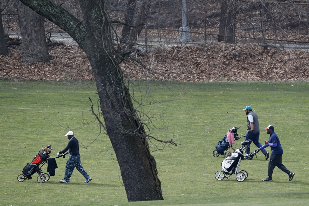 Golfers make their way down a fairway at Forest Park Golf Course, Friday, March 20, 2020, in New York. Even as the pandemic has shuttered restaurants,...