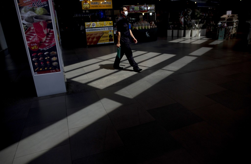 A security guard with a protective face mask walks at the entrance to a supermarket in Bangkok, Thailand, Tuesday, March 24, 2020. Most popular shoppi...