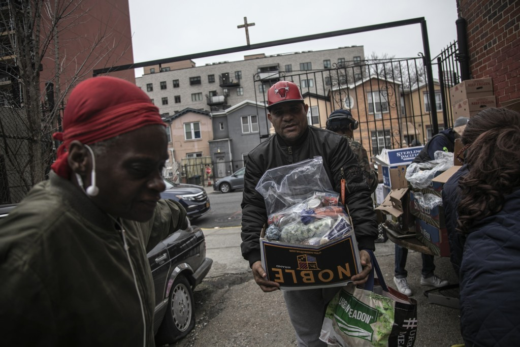 Surrounded by a few volunteers, a man carries food donations from St. Stephen Outreach in the Brooklyn borough of New York, on Friday, March 20, 2020....