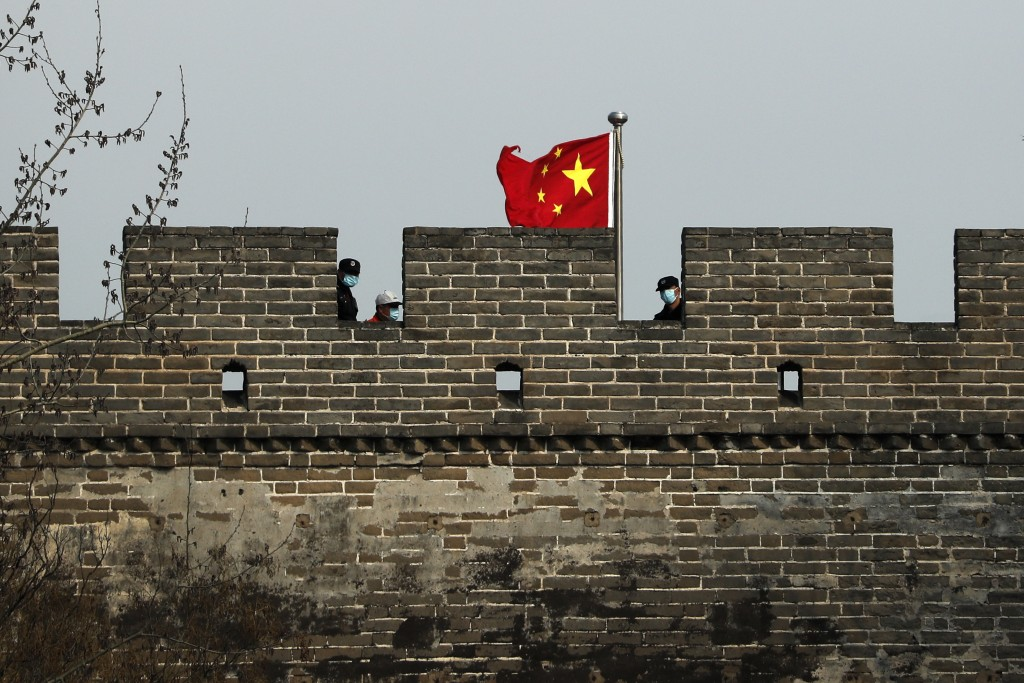 Security guards wearing protective face masks stand watch on the Badaling Great Wall of China after it reopened for business following the new coronav...