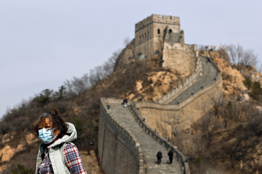 A woman wearing a protective face mask visits the Badaling Great Wall of China after it reopened for business following the new coronavirus outbreak i...