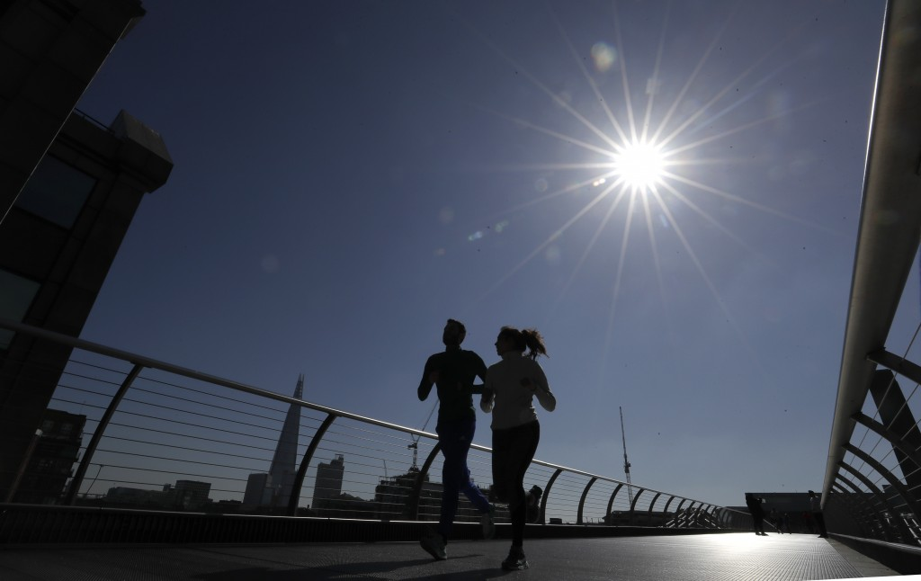 People run on Millenium Bridge over the River Thames in London, March 22, 2020. (AP Photo/Kirsty Wigglesworth)