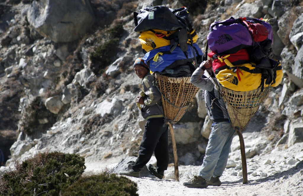 FILE - In this Sunday, Nov. 8, 2015, file photo, porters rest carrying the load of trekkers making their way back from Everest Base Camp, near Shomare...