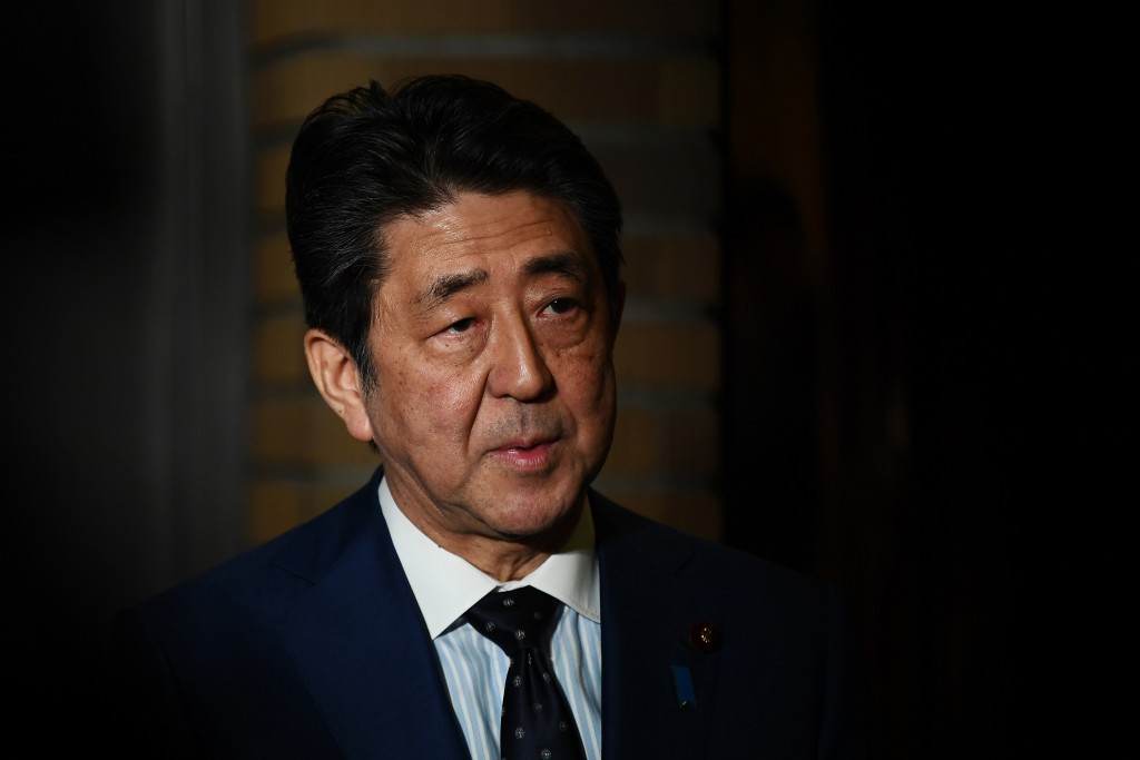 Japan's Prime Minister Shinzo Abe talks to journalists in front of the prime minister's residence in Tokyo, Tuesday, March 24, 2020. Abe says IOC pres...