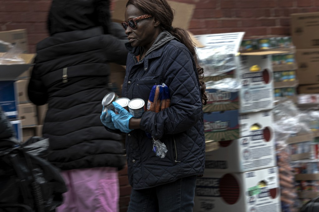 A volunteer carries canned food and a bag of carrots at St. Stephen Outreach in the Brooklyn borough of New York, on Friday, March 20, 2020. For decad...