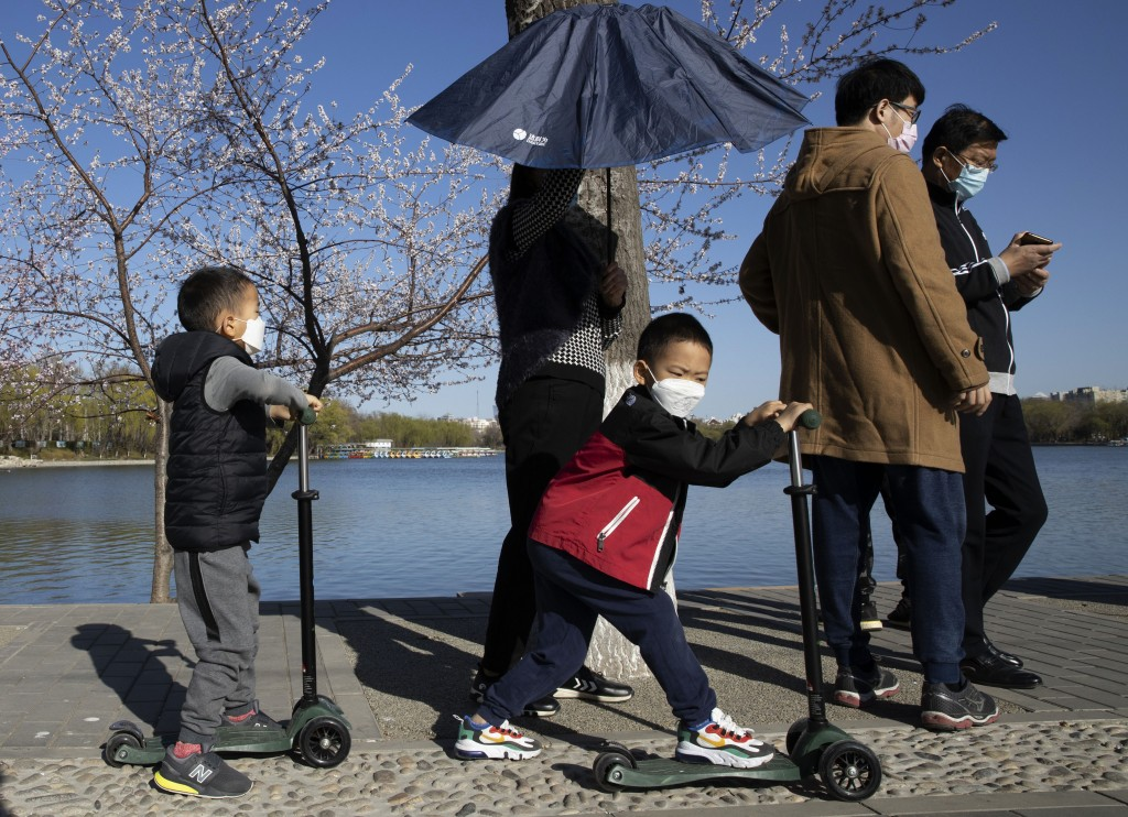 In this photo taken Thursday, March 19, 2020, visitors enjoy a sunny day at a park in Beijing, China. While many of the city's world-famous tourist si...