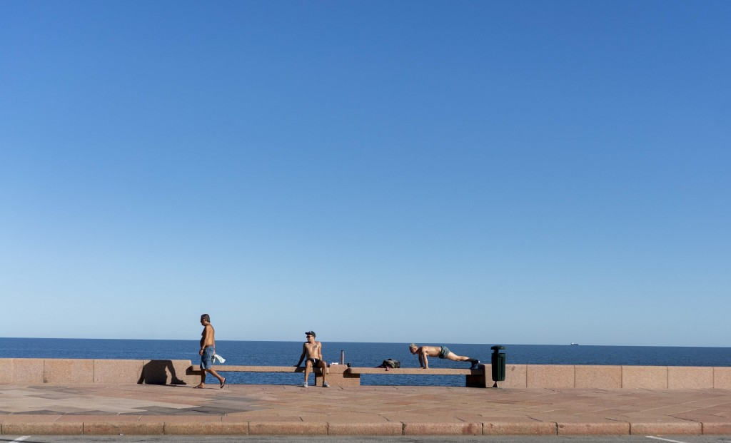 People exercise and relax in Montevideo, Uruguay, Saturday, March 21, 2020. (AP Photo/Matilde Campodonico)