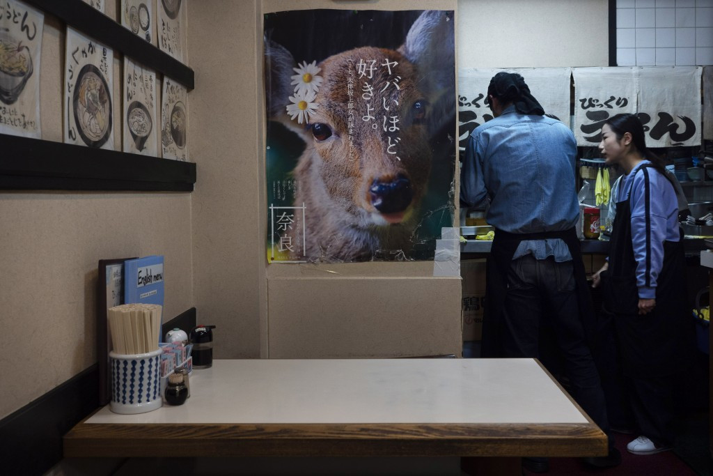 Two servers chat in a restaurant adorned with a poster showing a deer to promote the town's tourism in Nara, Japan, Tuesday, March 17, 2020. (AP Photo...