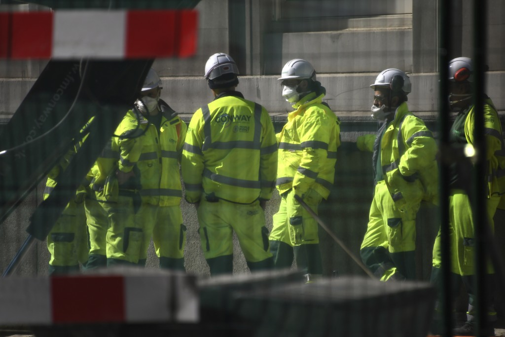 Construction workers wearing face masks seen through safety fencing work on a site near London Bridge in London, Tuesday, March 24, 2020. Britain's Pr...