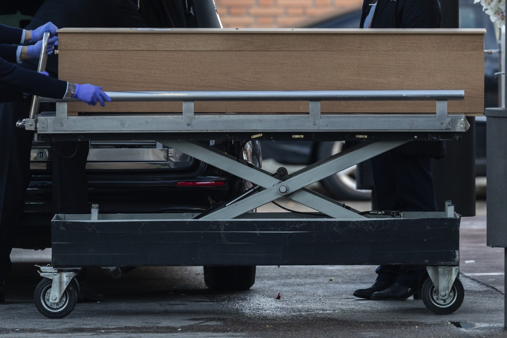 Undertakers carry a coffin of a person who died of COVID-19 at the La Almudena cemetery in Madrid, Spain, Monday, March 23, 2020. As cases in China eb...