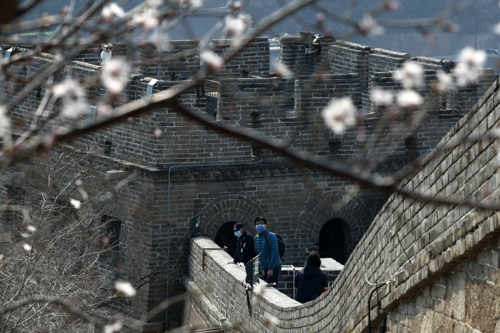 Visitors wearing protective face masks looks out from the Badaling Great Wall of China after it reopened for business following the new coronavirus ou...