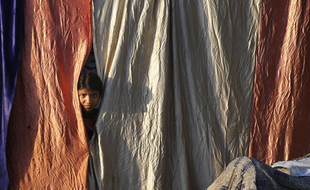 A girl living on the roadside looks out from her makeshift home during a lockdown to control coronavirus spread, in Prayagraj, India, Wednesday, March...