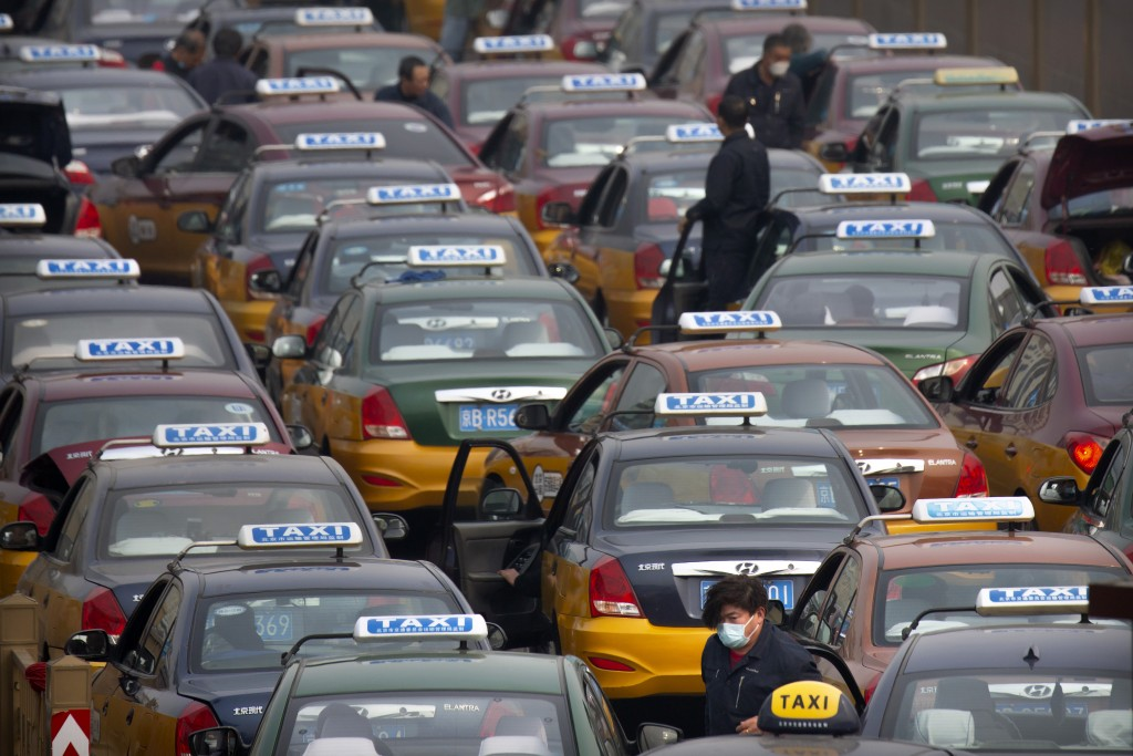 A taxi driver wearing a face mask stands in the taxi queue at the Beijing Railway Station in Beijing, Wednesday, March 25, 2020. Some train stations a...