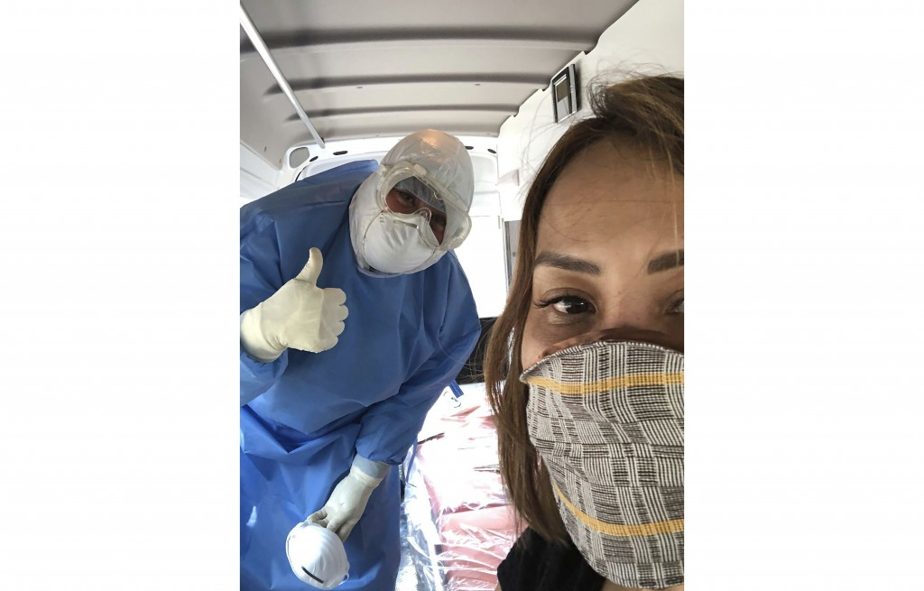 In this March 6, 2020, photo, Evie Navarro takes a selfie with a Health department personnel while undergoing testing after her husband Carlo Navarro ...