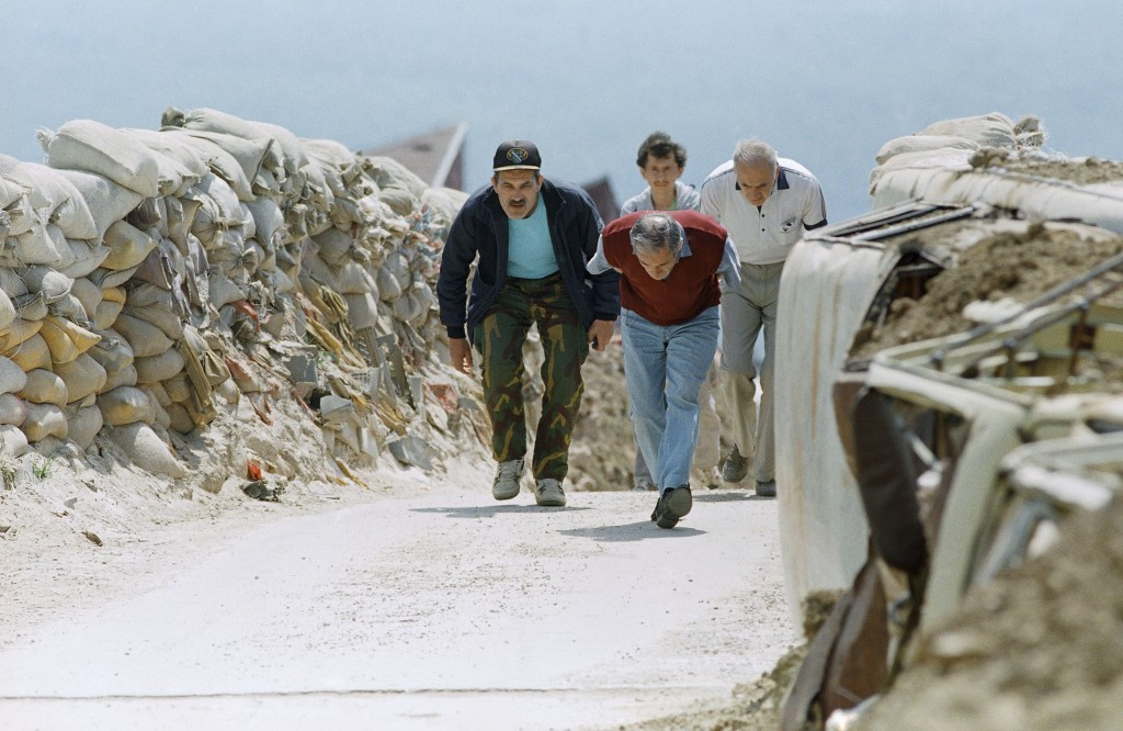 FILE - In this June 13, 1993 file photo, men run across the bridge into the Sarajevo suburb of Dobrinja in Sarajevo. The suburb was isolated from the ...