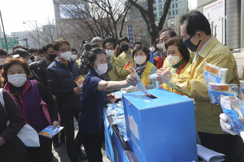 A woman puts an envelope containing a face mask into a charity box as South Korean Prime Minister Chung Se-kyun, right, watches during a campaign for ...