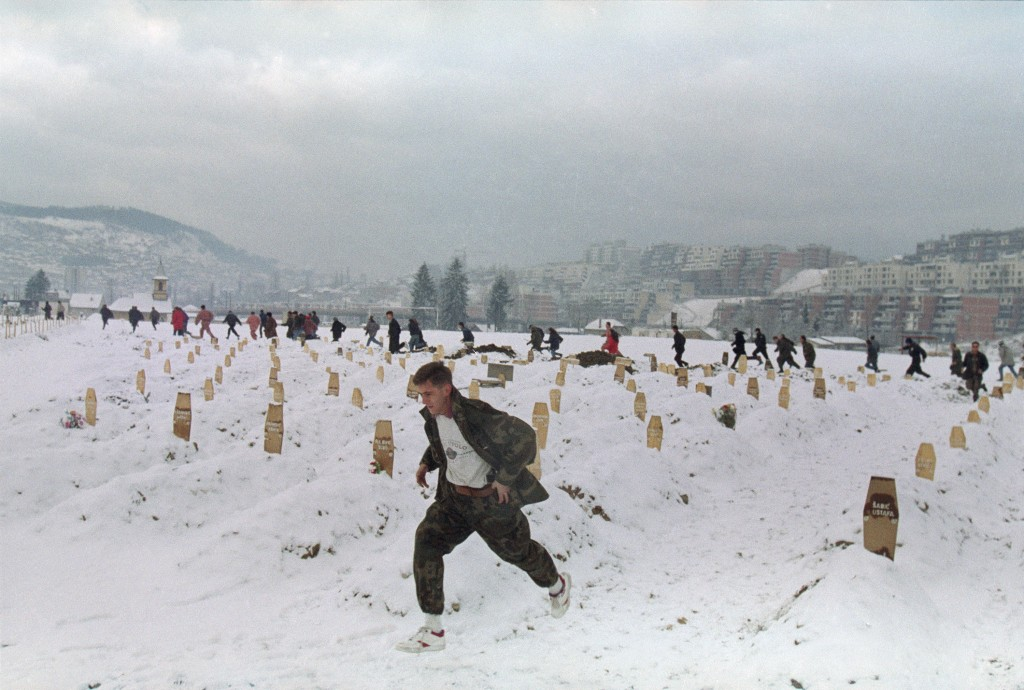 FILE - In this Feb. 20, 1993 file photo, a Bosnian soldier and other people in the background run for cover as Sarajevo's snow-covered military cemete...