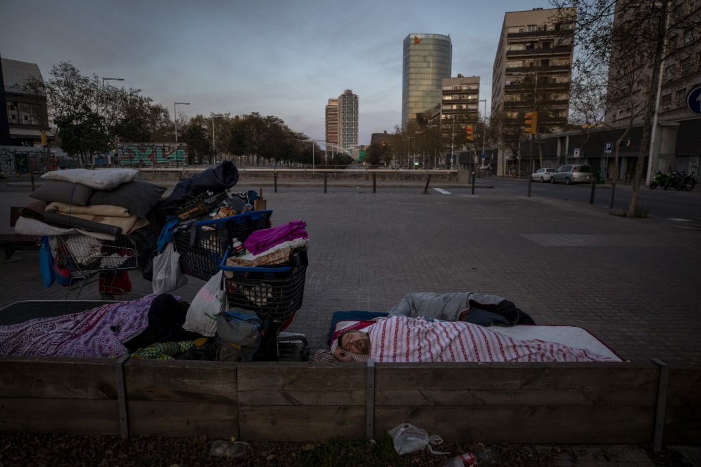 In this Friday, March 20, 2020 photo, Boris, 42, from Bulgaria, sleeps under a blanket in the street in Barcelona, Spain. While Spanish authorities te...