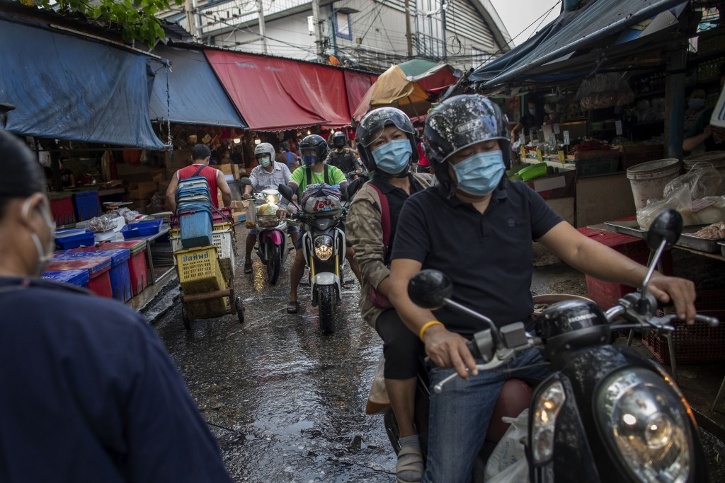 Thai people wearing protective masks ride through a wholesale market in Bangkok, Thailand, Wednesday, March 25, 2020. Thailand's government announced ...