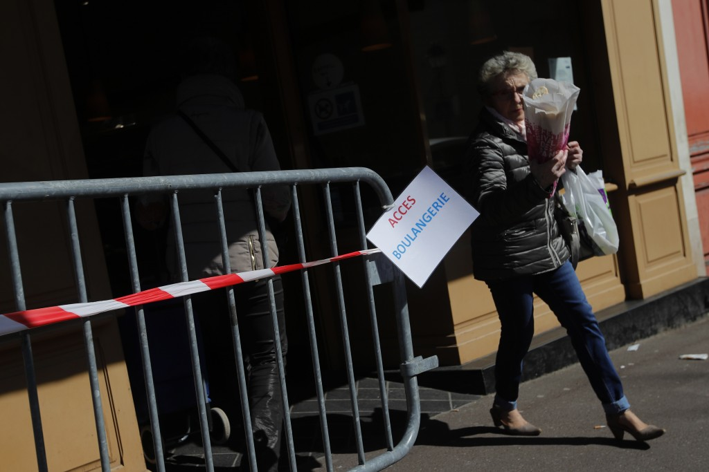 A woman leaves a bakery after buying bread in Ville d'Avray, outside Paris, Tuesday, March 24, 2020. French President Emmanuel Macron urged employees ...