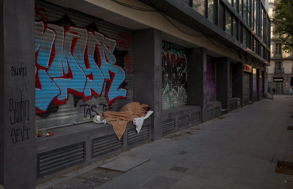 In this Friday, March 20, 2020 photo, Nasir, 37, from Pakistan, sleeps in an empty street in Barcelona, Spain. Authorities are scrambling to get as ma...