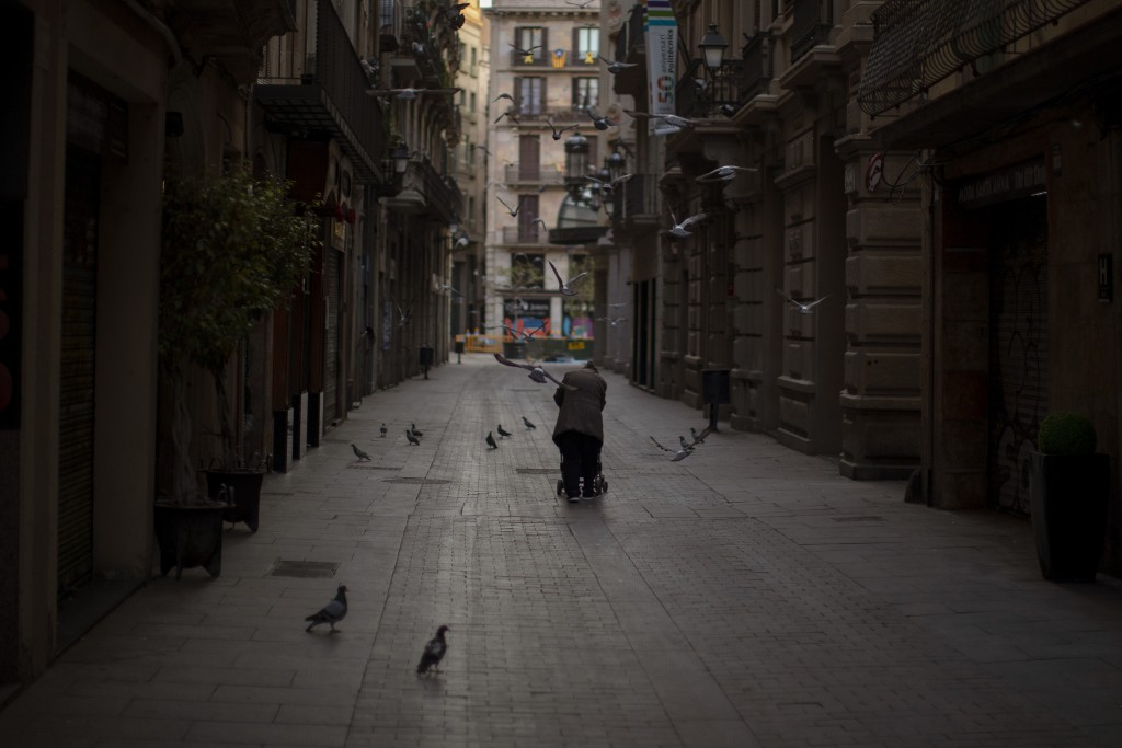 In this Saturday, March 21, 2020 photo, a woman pushes a cart with her belongings as she walks along an empty street in downtown Barcelona, Spain. Whi...