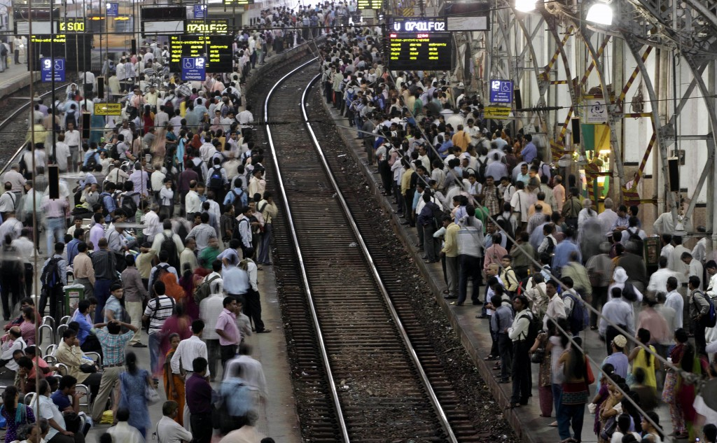 FILE - In this Wednesday, July 11, 2012, file photo, Indian commuters wait for trains at the Churchgate railway station in Mumbai, India. India's colo...