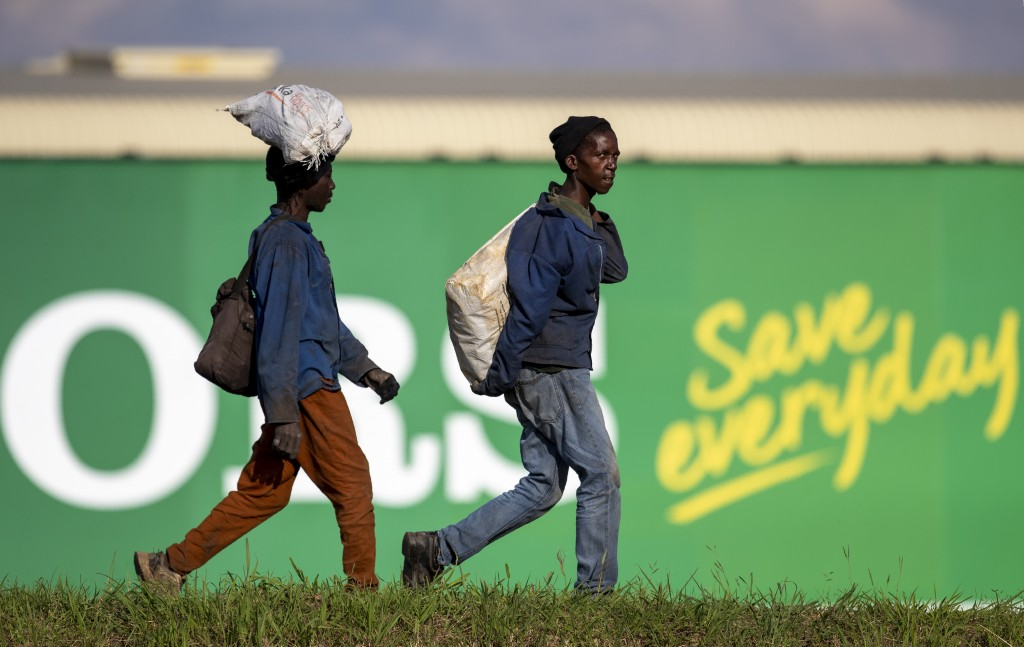 Men carrying recycling material walk in the industrial area in Daveyton, east of Johannesburg, South Africa, Tuesday, March 24, 2020, a day after it w...