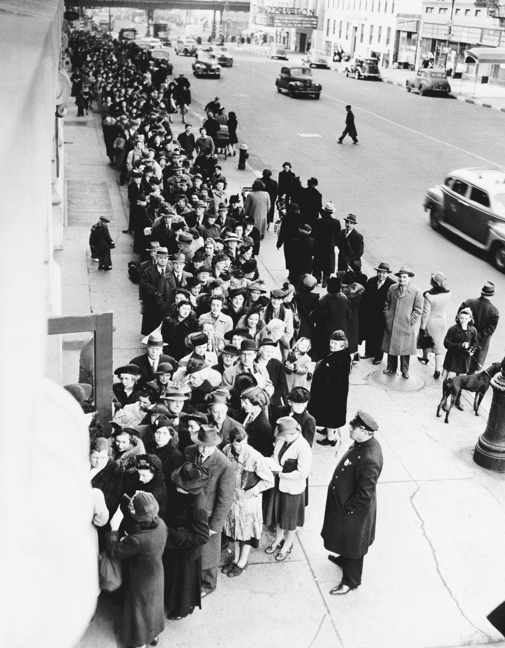 FILE - In this Feb. 23, 1943, file photo New Yorkers stand on long lines outside of schools all over the city to get their War Ration Book No. 2, duri...