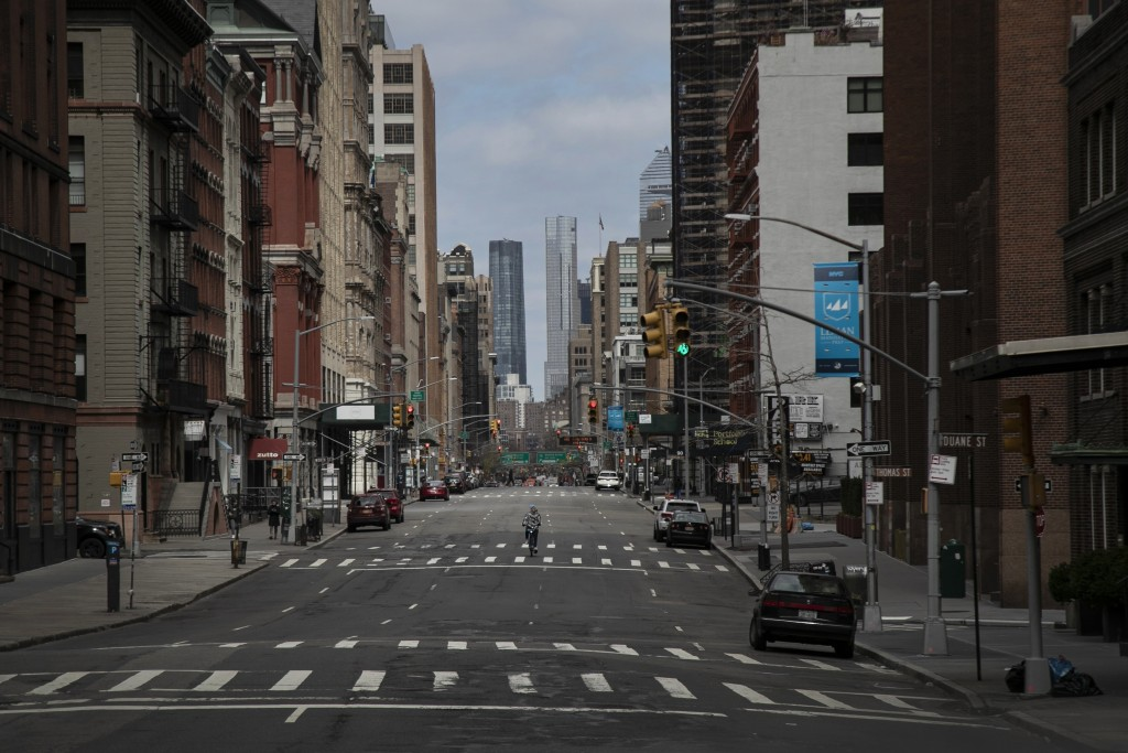 FILE - In this March 22, 2020, file photo, a cyclist rides his bicycle down the middle of a main road in downtown New York. World War II references ar...