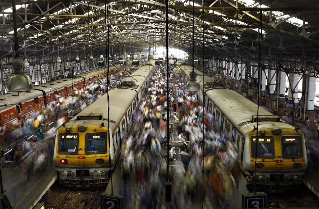 FILE - In this Feb. 11, 2013, file photo, Indian commuters get off trains at the Church Gate railway station in Mumbai, India. India's colossal passen...