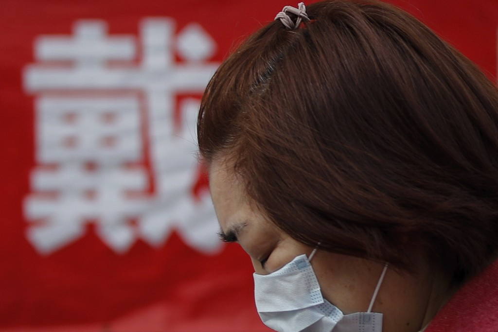FILE - In this Wednesday, March 18, 2020, file photo, a woman wearing a protective face mask to prevent the new coronavirus outbreak walks by a propag...