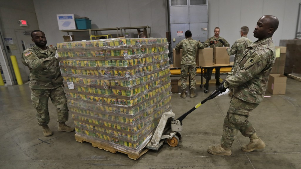 Ohio National Guard Specialist Scott Eubanks, right, and Corp. Tommie Davis move a skid of peaches to prepare for repackaging emergency food boxes for...