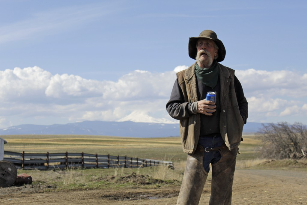 In this photo taken March 20, 2020, cattle rancher Mike Filbin stands on his property in Dufur, Ore., after herding some cows and talks about the impa...