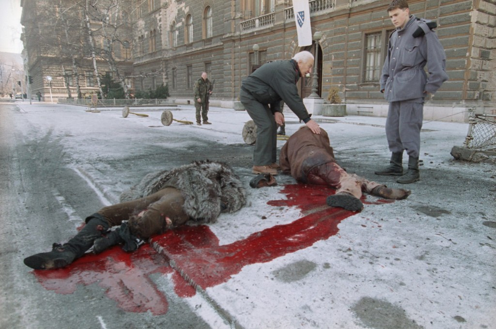 FILE - In this  Jan. 30, 1993 file photo, Bosnian soldiers help injured people laying on the street in front of the Bosnian presidency after a shell h...