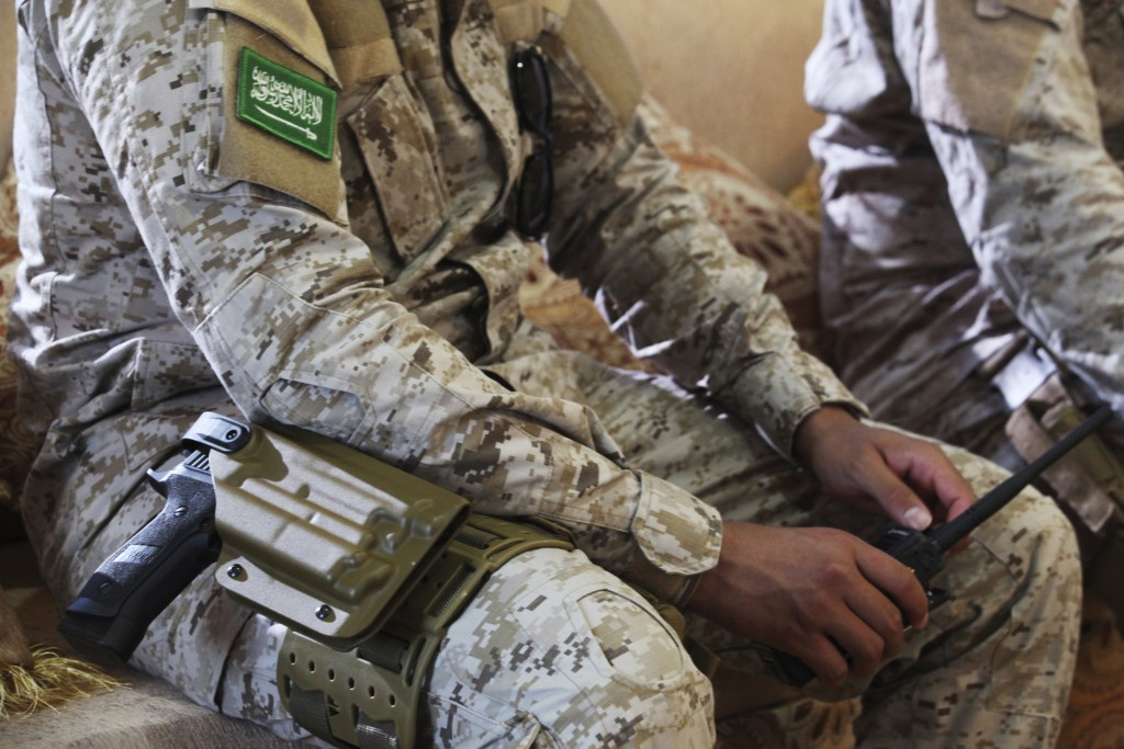 FILE - In this Nov. 28, 2018 file photo, an armed Saudi soldier holds a walkie-talkie near Mukalla, Yemen, at an airport now serving as a military bas...
